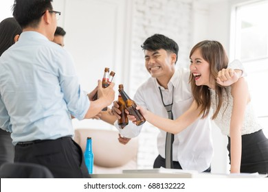 The colleague celebrating having beer in work place office. They are smiling and talking.Motion blur movement,In selective focus on bottles.