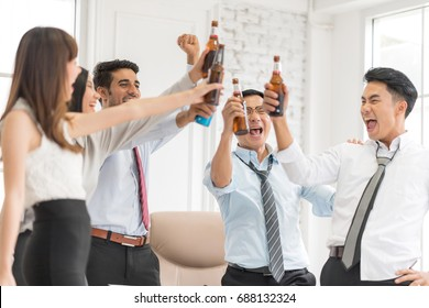 The colleague celebrating having a drink after work.Standing around with lifting their bottles of beer all happy smiling and talking.Motion blur movement,In selective focus on people face