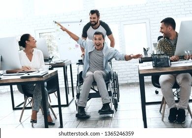 A colleague rolls a person in a wheelchair around the office. They have fun and laugh. People working and spending time in bright office.
