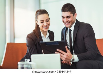 Colleague Team businessman and businesswoman sitting in armchairs using digital tablet