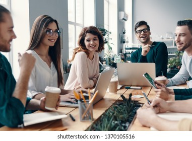 Colleagues become friends. Group of young modern people in smart casual wear discussing something and smiling while working in the creative office
