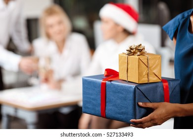 Colleagues celebrating christmas party in office smiling giving presents.