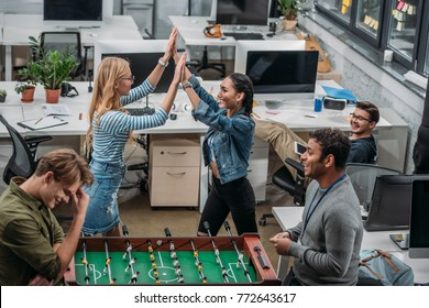 colleagues celebrating victory in table soccer at modern office