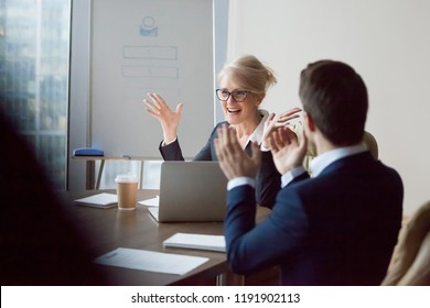 Colleagues congratulating middle aged female boss with high work achievement at meeting, employees applaud to successful businesswoman for contract closing, workers greet director with success