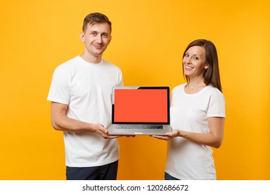 Colleagues couple in white print t-shirt hold laptop pc computer, blank empty screen isolated on yellow wall background. Voluntary free work, assistance help charity grace teamwork concept. Mock up.