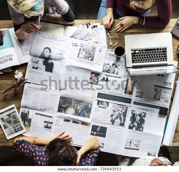 Colleagues discussing newspaper articles