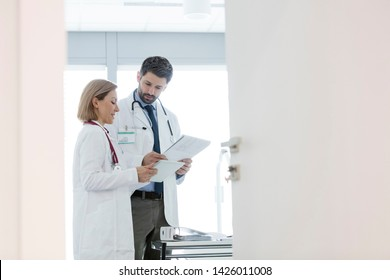 Colleagues discussing over medical records at desk seen through open door in hospital