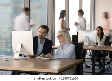 Colleagues employees working together with computer in modern corporate office, serious company executive managers use desktop collaborate consult about online business project looking at monitor