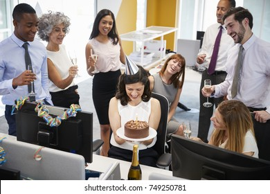 Colleagues gathered at womanâ??s desk to celebrate a birthday