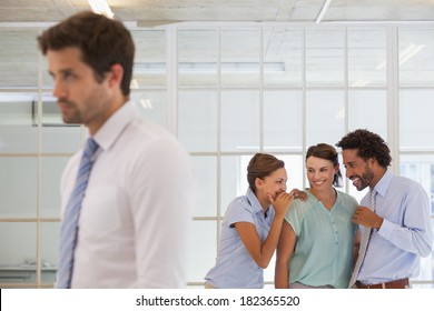 Colleagues gossiping with sad young businessman in foreground at a bright office