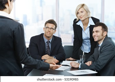 Colleagues listening to businesswoman's report in meeting room in office.