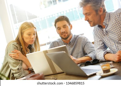 Colleagues looking at computer in coworking space