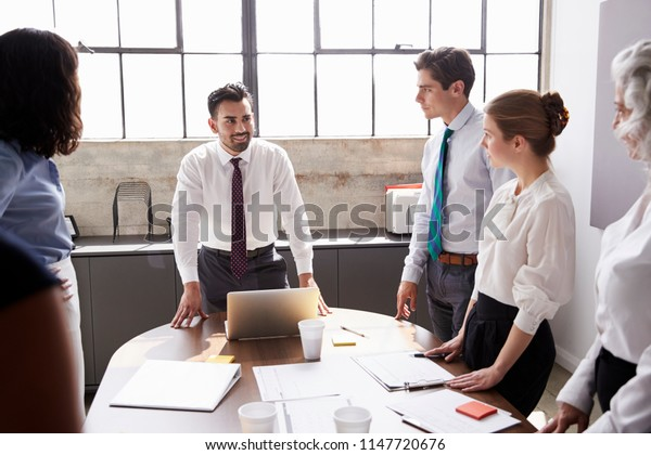 Colleagues looking to Hispanic male manager in meeting room