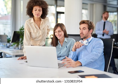 Colleagues looking at laptop and helping each other to solve a problem. Office interior.
