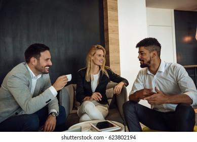 Colleagues making a coffee break in an office lobby.