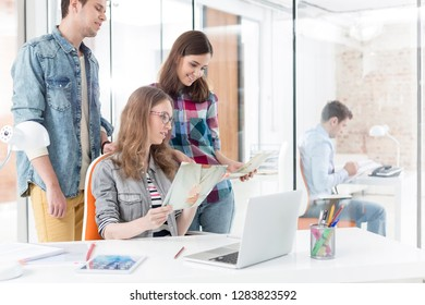 Colleagues with photographs and laptop in office