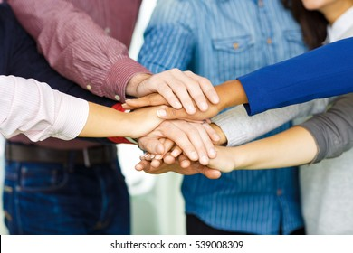 Colleagues piling their hands together. Cropped closeup shot of a group of mixed race businesspeople putting their hands together in unity