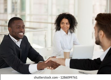 Colleagues shaking hands greeting each other during meeting. Diverse partners businessmen company owner client handshaking express respect sitting together with adorable colleague mixed race female