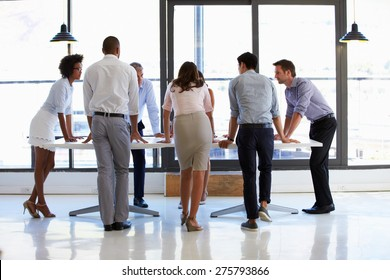 Colleagues standing around a conference table