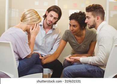 Colleagues supporting tensed businessman in creative office