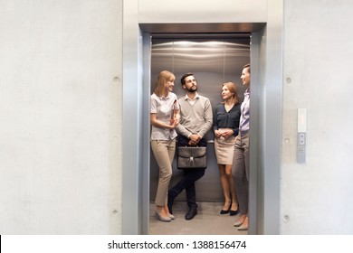 Colleagues talking while standing in elevator at office