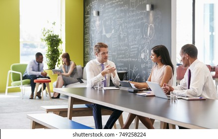 Colleagues talking at work in an informal meeting area
