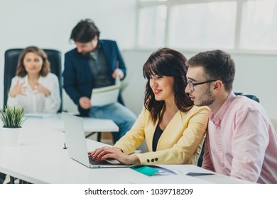 Colleagues working at office in front of computer