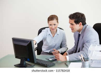 Colleagues working together on a computer against grey background