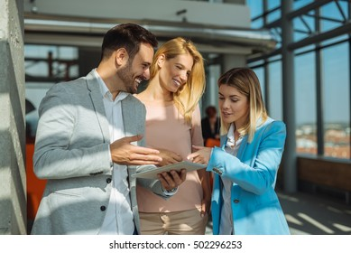 Colleagues working together on a tablet in an office.