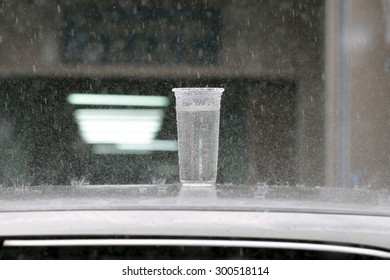 Collect rainwater. Plastic cup on car roof collecting rainwater in rainy day, Concept, Selective focus point on Plastic cup