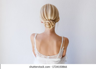 Collected blonde hair in a hairstyle on a light background. Hairstyle for the bride of the blonde