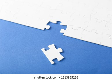 Collected white puzzles on a blue background with one missing piece close up. Symbol teamwork on the result.