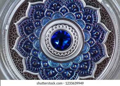Collectible pure silver coin decorated with a blue sapphire and mandala as a precious metal investment