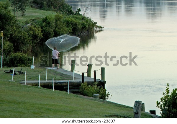 Collecting bait with a cast net for fishing.