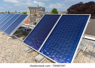 Collecting electricity with solar panels on a roof in the dutch city of Leiden.