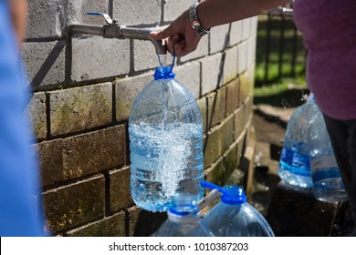 Collecting natural spring water with 5 litre plastic water bottle at Newlands natural spring Cape Town South Africa