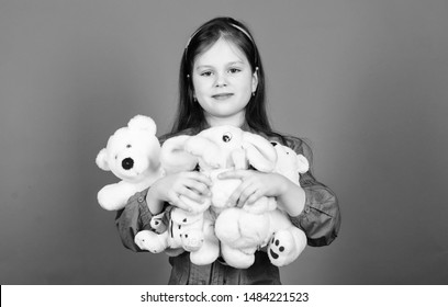Collecting toys hobby. Cherishing memories of childhood. Childhood concept. Small girl smiling face with toys. Happy childhood. Little girl play with soft toy teddy bear. Lot of toys in her hands.