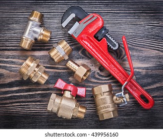 Collection of adjustable pipe wrench brass fittings water valve on wood board plumbing concept.