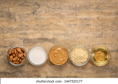 collection of almond super foods: nuts, flour, slices, milk, oils and butter - top view of small glass bowls over textured bark paper against textured bark paper with a copy space