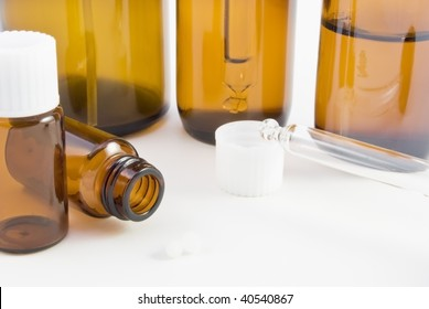 A collection of amber glass bottles (spray, dropper and pill) and pillules used in homeopathic pharmacy.