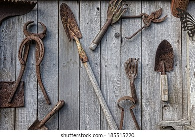 A collection of antique rusted old garden and ranch tools hang on a weathered shed wall in an artistic collage.