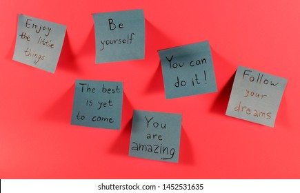 Collection of blue sticky notes with inspirational quotes on neon pink background. Handwritten positive reminder/advice. Concept for confidence, courage and motivation. Sign of moral support.