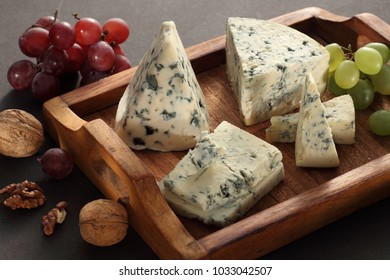 Collection of blue and white mold French and Italian cheeses on cheese board served with fruits and nuts / Bleu d' Auvergne / Gorgonzola