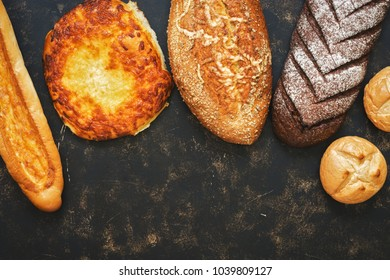 A collection of bread with sprinkling and cheese on a rustic dark background. Copy space, top view