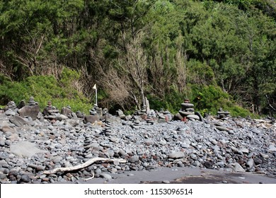 A collection of cairns built on the rocky shore of Pololu Valley in front of lush vegetation in North Kohala, Hawaii, USA