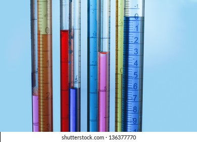 collection of calibrated pipettes filled with colored fluid on a blue background