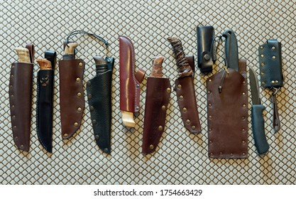 Collection of camping knives: 7 home made leather sheaths, 5 home made wooden knife handles, 2 folding knives in sheaths.( scandinavian rune letters on the 6th sheath are from ancient text and