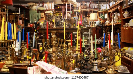A collection of candle holders piled on top of each other at a second-hand/antique store.