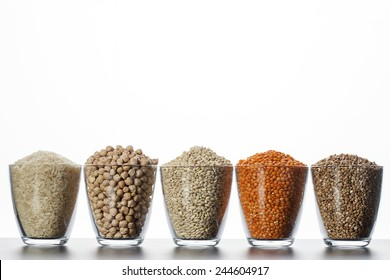Collection of cereals and legumes in transparent cup on a white background