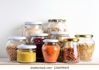 Collection of cereals in storage jars in pantry.